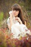 Mujer joven que soña entre las hojas de otoño Foto de archivo
