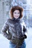 Mujer joven que sonríe bajo nevadas Foto de archivo libre de regalías