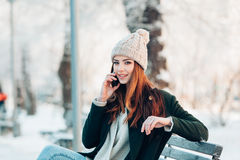 Mujer joven que sonríe con el teléfono elegante y el invierno Imágenes de archivo libres de regalías