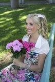 Mujer joven que sonríe con las flores Imagenes de archivo