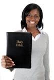 Mujer joven que sonríe con una biblia Imagen de archivo libre de regalías