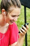 Mujer joven que sonríe en el teléfono Imagen de archivo