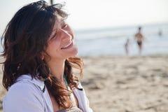 Mujer joven que sonríe en la playa Imágenes de archivo libres de regalías