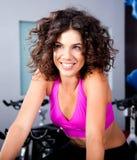 Mujer joven que sonríe haciendo ejercicio cardiio Imágenes de archivo libres de regalías
