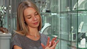 Mujer joven que sonríe, intentando en el anillo de diamante, haciendo compras en la joyería almacen de metraje de vídeo