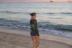Mujer joven que sonríe mientras que camina en la playa Imagenes de archivo