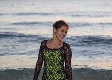 Mujer joven que sonríe mientras que camina en la playa Fotos de archivo