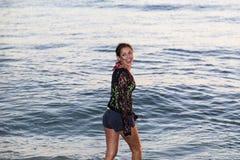 Mujer joven que sonríe mientras que camina en la playa Foto de archivo