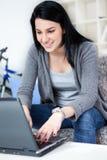 Mujer joven que sonríe mientras que usa la computadora portátil Fotografía de archivo