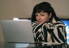 Mujer joven que sonríe mientras que se sienta en casa por la pantalla del ordenador portátil imagen de archivo
