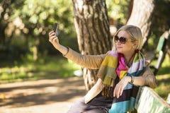 Mujer joven que sonríe para un autorretrato (selfie) en su smartphone, sentándose en banco en el parque Imágenes de archivo libres de regalías