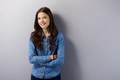 Mujer joven que sonríe por la pared gris Imágenes de archivo libres de regalías