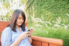 Mujer joven que sonríe y el sentarse que manda un SMS del teléfono celular en un banco de parque en otoño o caída Imagen de archivo