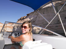 Mujer joven que sonríe y que conduce el barco Foto de archivo libre de regalías