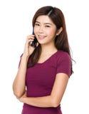 Mujer joven que sonríe y que habla en su teléfono celular Fotos de archivo libres de regalías