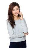 Mujer joven que sonríe y que habla en su teléfono celular Fotos de archivo