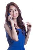 Mujer joven que sonríe y que manda un SMS en su teléfono móvil Fotos de archivo