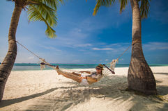 Mujer joven que sonríe y que se relaja en una hamaca por la playa Imágenes de archivo libres de regalías