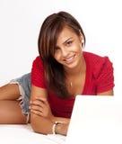 Mujer joven que sonríe en la computadora portátil Fotografía de archivo libre de regalías