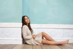 Mujer joven que sonríe y que se sienta en el piso de madera en casa Imágenes de archivo libres de regalías