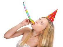 Mujer joven que sopla en ventilador del cuerno del partido Fotografía de archivo libre de regalías