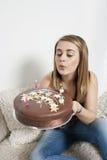 Mujer joven que sopla hacia fuera velas en la torta de cumpleaños Fotografía de archivo