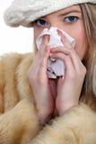 Mujer joven que sopla su nariz Imagenes de archivo