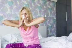 Mujer joven que sopla su nariz en papel seda mientras que se sienta en cama Imagen de archivo libre de regalías