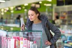 Mujer joven que sopla su nariz mientras que en una farmacia moderna Fotografía de archivo libre de regalías