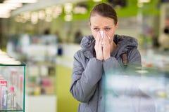 Mujer joven que sopla su nariz mientras que en una farmacia moderna Fotos de archivo