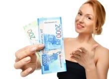 Mujer joven que soporta el dinero del efectivo dos mil y cientos rublos rusas de ganador disponible de las notas sorprendido foto de archivo