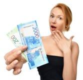 Mujer joven que soporta el dinero del efectivo dos mil y cientos rublos rusas de ganador disponible de las notas sorprendido imagenes de archivo