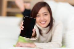 Mujer joven que soporta su teléfono móvil Imagenes de archivo