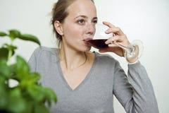 Mujer joven que sorbe el vino rojo Fotos de archivo libres de regalías