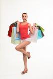 Mujer joven que sostiene bolsos de compras Foto de archivo libre de regalías