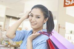 Mujer joven que sostiene bolsos de compras con la mano en su pelo, mirando la cámara en una alameda Imagen de archivo libre de regalías