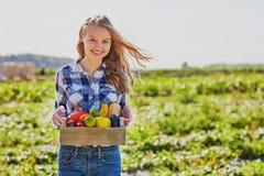 Mujer joven que sostiene el cajón de madera con las verduras Imagenes de archivo
