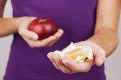 Mujer joven que sostiene el caramelo y la manzana Imágenes de archivo libres de regalías