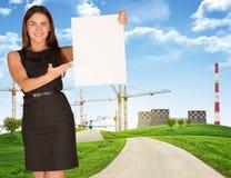 Mujer joven que sostiene el cartel en blanco con industria encendido Fotos de archivo libres de regalías
