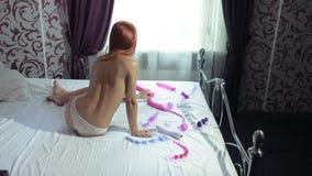 Mujer joven que sostiene el consolador en cama La muchacha elige un vibrador Porción de juguetes del sexo metrajes