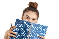 Mujer joven que sostiene el cuaderno y el lápiz Foto de archivo