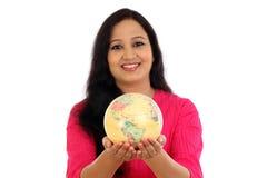 Mujer joven que sostiene el globo del mundo Foto de archivo