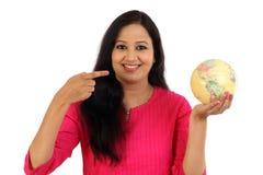 Mujer joven que sostiene el globo del mundo contra blanco Fotos de archivo