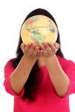 Mujer joven que sostiene el globo del mundo contra blanco Foto de archivo libre de regalías