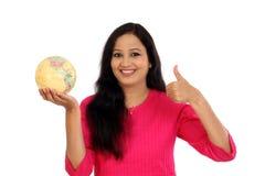 Mujer joven que sostiene el globo del mundo contra blanco Imagen de archivo libre de regalías