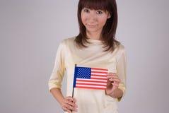 Mujer joven que sostiene el indicador americano Foto de archivo libre de regalías