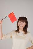 Mujer joven que sostiene el indicador chino Fotografía de archivo