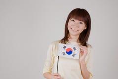Mujer joven que sostiene el indicador coreano Foto de archivo