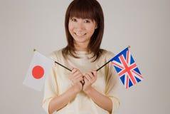 Mujer joven que sostiene el indicador japonés y el indicador británico Imagen de archivo