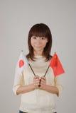 Mujer joven que sostiene el indicador japonés y el indicador chino Imágenes de archivo libres de regalías